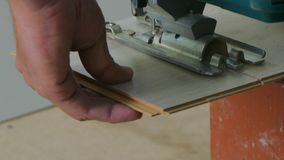 Jig saw to cut laminate. Hands using electric jig saws saw the laminate stock video