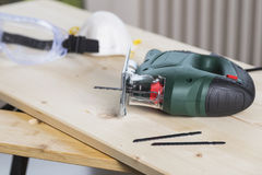 Jig Saw on workbench. Jig saw power tool with mask and goggles on workbench Stock Photo