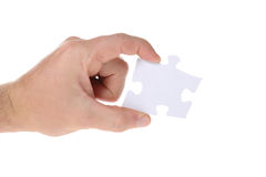 Jigsaw. Hand hold a piece of jigsaw puzzle isolated on white Stock Image