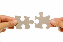 Jigsaw. Hands joining two jigsaw pieces together royalty free stock photo