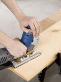Jigsaw and cutting a piece of wood. Human hand holding jigsaw and cutting a piece of wood Royalty Free Stock Photos