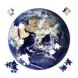 Jigsaw Earth. Earth jigsaw almost complete with some pieces still left to place Stock Photo