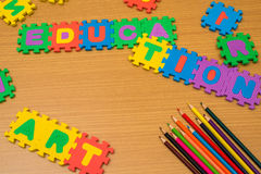 Jigsaw education background and multi colored pencils Stock Photos