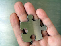 Jigsaw in Hand. Metallic jigsaw piece on a human hand Stock Images