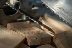 Jigsaw and hand saw blades above wooden bricks stock image