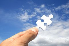 Jigsaw Key. Hand Holding jigsaw piece instead of key royalty free stock photo