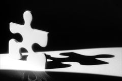 Jigsaw Man Shadow. White jigsaw piece in beam of light with shadow behind Stock Images