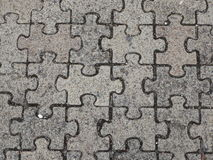 Jigsaw Paving stone background. A connecting block of grey concrete jigsaw shaped paving stones Stock Photo