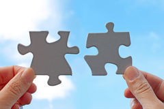 Jigsaw piece against sky. Hands holding jigsaw pieces coming together against a sky background royalty free stock photos