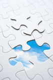 Jigsaw piece with sky in hole, conceptual image Royalty Free Stock Photography
