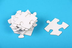 Jigsaw Pieces. Blank white jigsaw pieces stacked on a blue paper background as a concept for challenges and solutions in business Royalty Free Stock Images