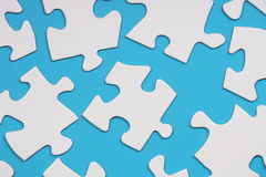 Jigsaw Pieces. White Jigsaw pieces scattered on a blue paper background in a random pattern Royalty Free Stock Photography