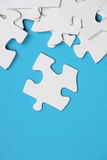 Jigsaw Pieces. White Jigsaw pieces on a blue paper background with room for copy space Stock Photos