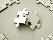 Jigsaw pieces. Two jigsaw pieces on a jigsaw frame stock photography
