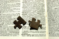 Jigsaw pieces on a dictionary. A picture of two jigsaw pieces placed on top of the open pages of a dictionary Stock Photos