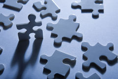 Jigsaw Pieces with Dramatic Light. Backlit jigsaw puzzle pieces with one standing up and looking anthropomorphic Stock Images