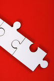 Jigsaw pieces on red. Lose up of two joined plain white jigsaw pieces on a bright red background. Taken in vertical format Royalty Free Stock Photo
