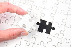 Jigsaw puzzle. A man inserting the final puzzle piece of a white jigsaw stock photo