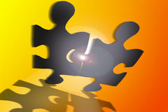 Jigsaw puzzle. An image showing two pieces of jigsaw holding each other up against a yellow lens flare background Royalty Free Stock Image