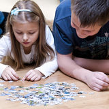 Jigsaw puzzle brother and sister. Brother and sister playing jigsaw puzzle together. Square composition Stock Image