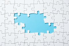 Jigsaw puzzle game piece on blue background for business theme design. White jigsaw puzzle game pieces on blue background form a banner for business theme design stock image