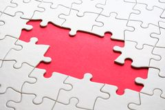 Jigsaw puzzle game piece on red background for business theme design. White jigsaw puzzle game pieces on red background form a banner for business theme design stock images
