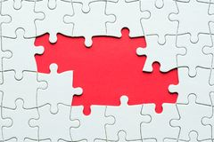Jigsaw puzzle game piece on red background for business theme design. White jigsaw puzzle game pieces on red background form a banner for business theme design stock image