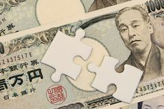 Jigsaw puzzle on Japanese Yen banknotes money using as Japan economic problem solving or key to get success in financial.  stock photography