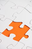 Missing Jigsaw Piece. A jigsaw puzzle made up of blank white pieces with a missing piece on an orange paper background Royalty Free Stock Images