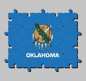 Jigsaw puzzle of Oklahoma flag in Buffalo-skin shield with seven eagle feathers on a sky blue field. royalty free illustration