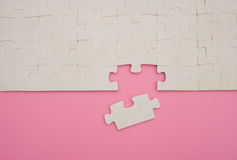 Jigsaw puzzle with one piece loose on pink Stock Photos