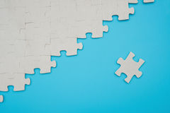Jigsaw puzzle with one piece separated on blue background Royalty Free Stock Photo