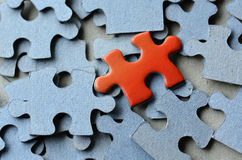 Jigsaw puzzle. Orange puzzle pice standing above the rest of puzzle pieces. Conceptual photograph to display business, personal, financial success, or a Stock Image