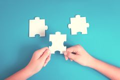 Jigsaw puzzle piece in a hand royalty free stock image