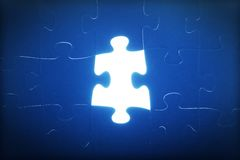 Jigsaw puzzle piece missing. Light glowing. Solution Stock Photography