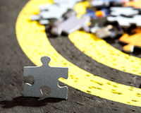 Jigsaw Puzzle Piece on Old Yellow Target Stock Photo