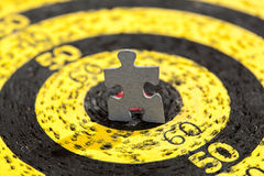 Jigsaw Puzzle Piece on Yellow Old Target. Jigsaw puzzle piece in shape of a standing man in a center of old yellow target Royalty Free Stock Image