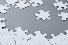 Jigsaw puzzle pieces. Loose jigsaw puzzle pieces on grey background Stock Photos
