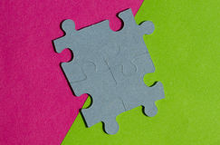 Jigsaw Puzzle pieces on border between pink and green background Royalty Free Stock Photography
