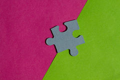Jigsaw Puzzle pieces on border between pink and green background Stock Photos