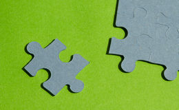Jigsaw puzzle pieces on bright green background. Horizontal view with copy space Royalty Free Stock Photo