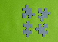 Jigsaw puzzle pieces on bright green background, horizontal view. With copy space Stock Photography