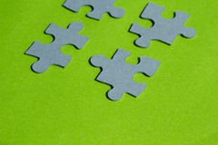 Jigsaw puzzle pieces on bright green background. Horizontal view with copy space Stock Photos