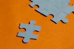 Jigsaw puzzle pieces on bright orange background Royalty Free Stock Images