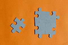 Jigsaw puzzle pieces on bright orange background Royalty Free Stock Image