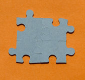Jigsaw puzzle pieces on bright orange background Stock Photo