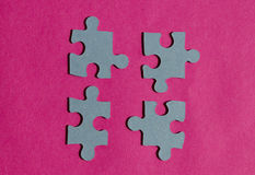 Jigsaw puzzle pieces on bright pink background Stock Images