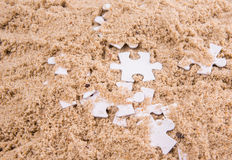 Jigsaw Puzzle Pieces Buried In Sand VI Stock Image
