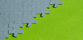 Jigsaw puzzle pieces  on green background. With copy space Royalty Free Stock Photos