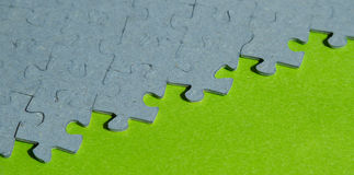Jigsaw puzzle pieces  on green background. With copy space Stock Photography